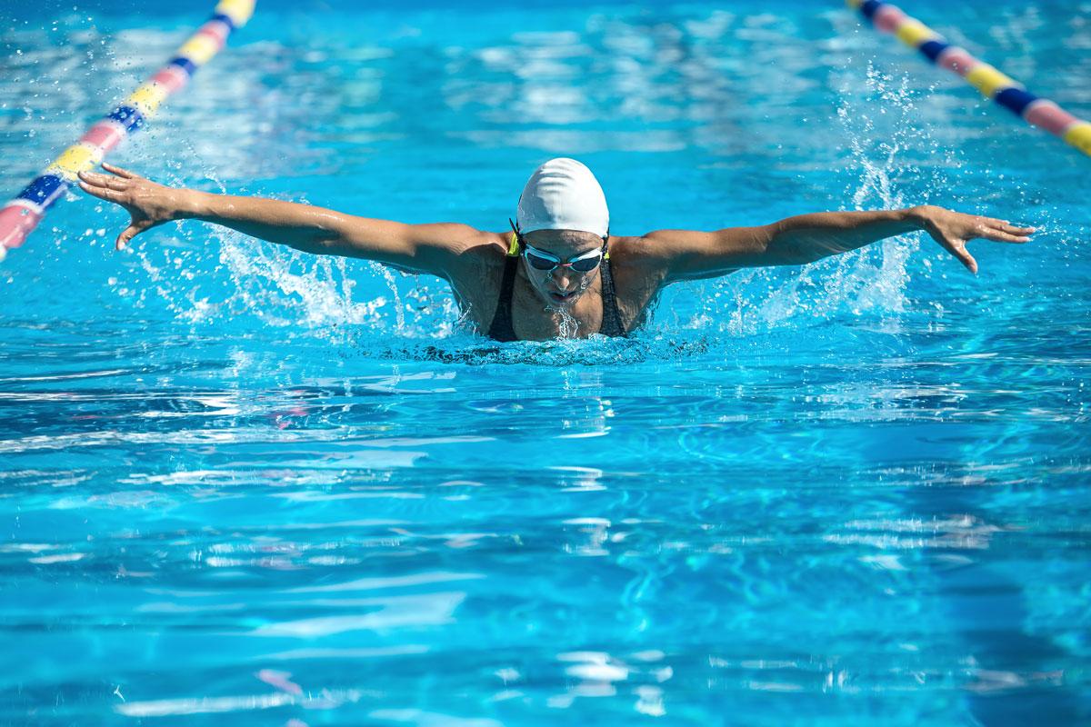 Пловец плывет баттерфляем в бассейне
