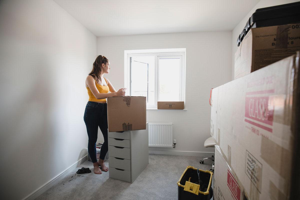 Девушка разбирает коробки в новом доме