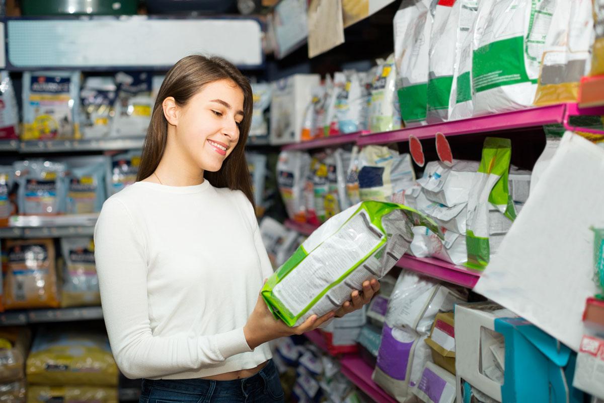 Девушка в магазине выбирает корм