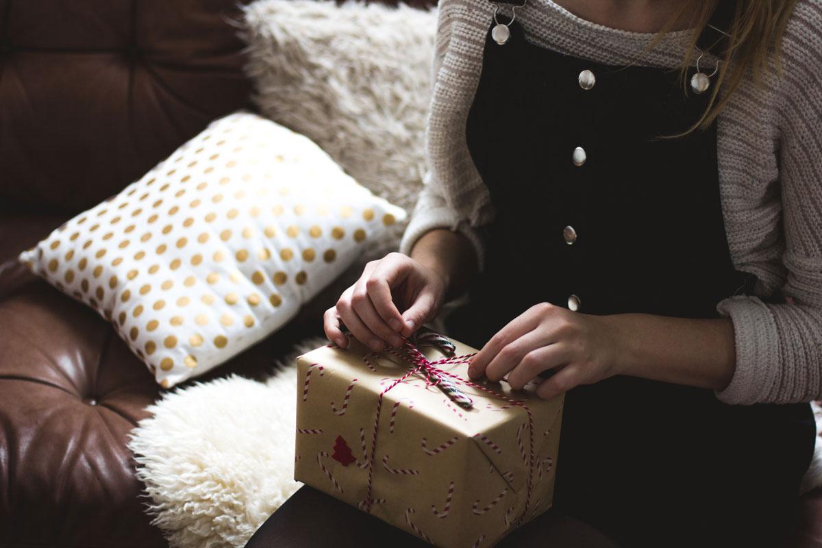 Девушка упаковывет подарок