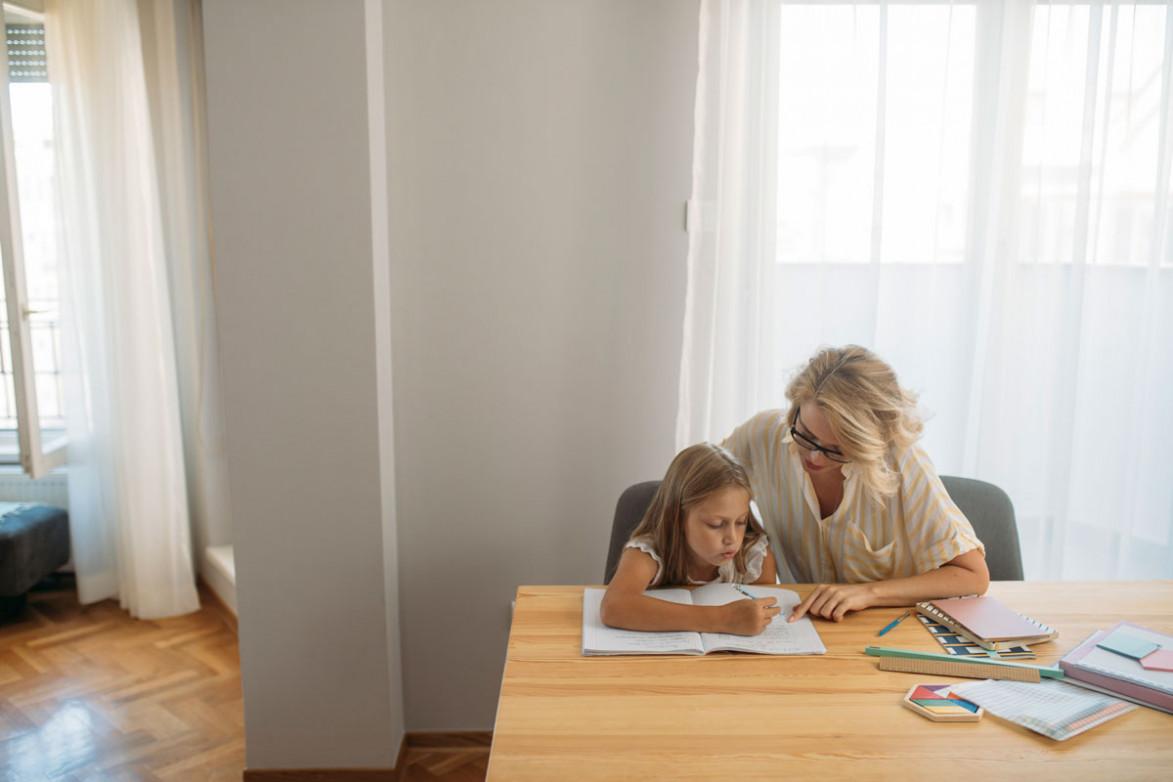 Женщина делает уроки с ребенком
