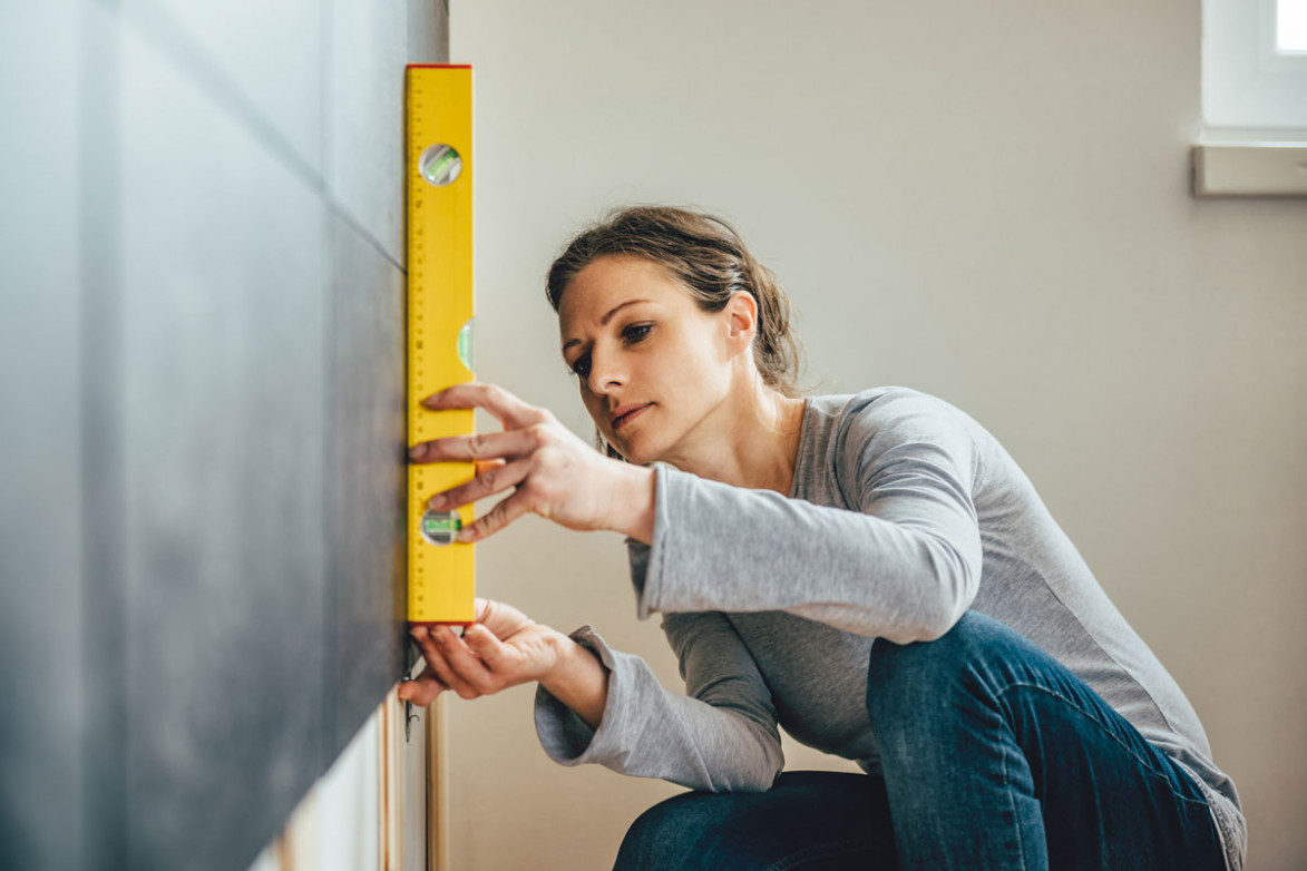 Женщина проверяет стену уровнем