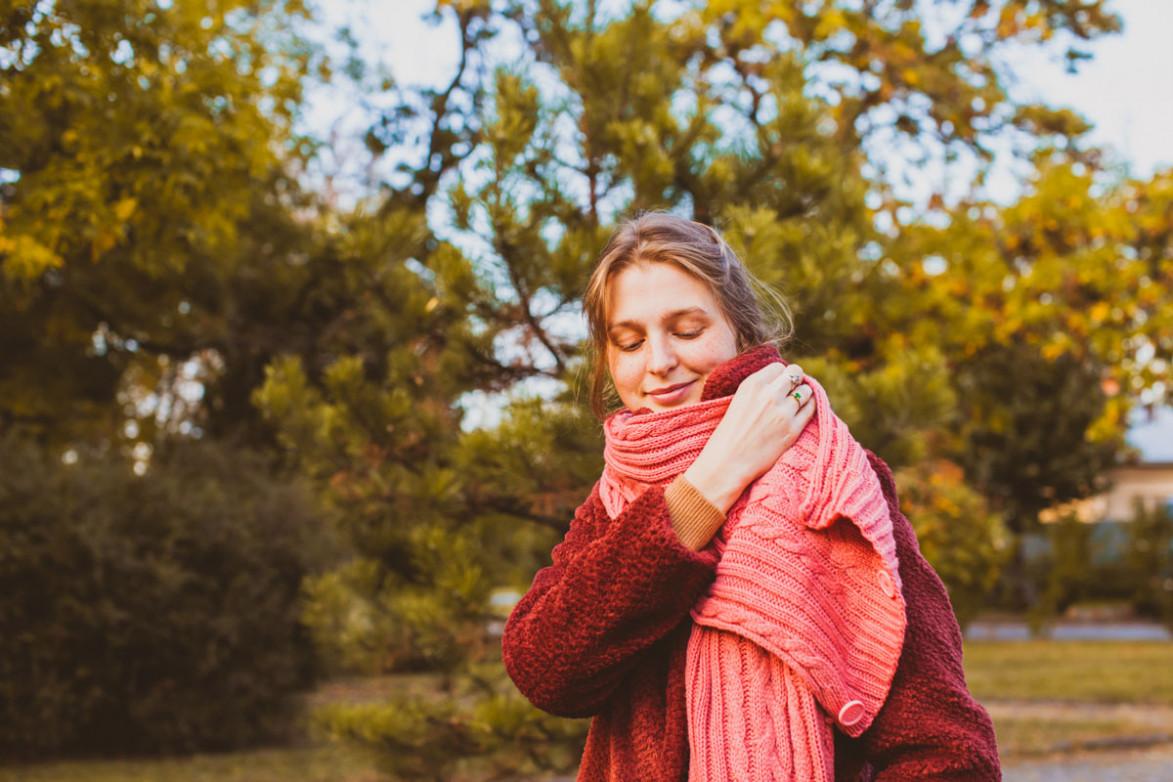 Девушка в осеннем парке кутается в шарф